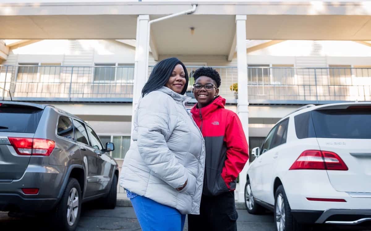 Formerly homeless black woman smiling in front of new home with her teenage son
