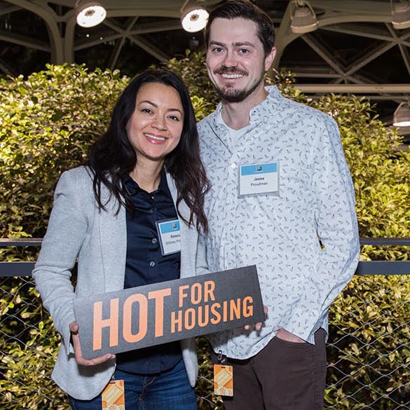 "Two champion donors pose for photo holding a sign that reads ""hot for housing"""