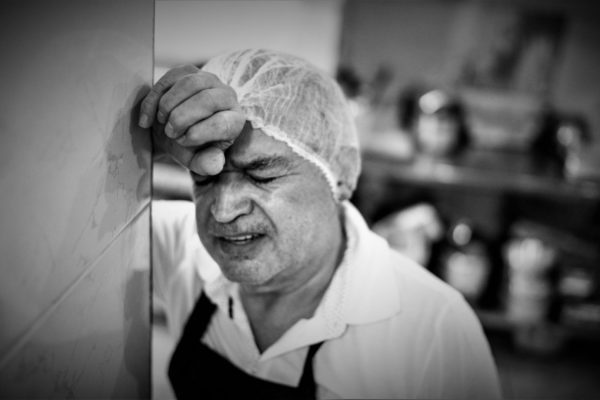 A kitchen worker looking tired and worried.