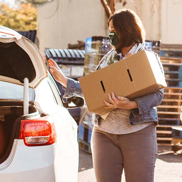 A person holding a box of food approaches a car with the trunk open