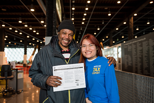 A tax volunteer poses with a person who holds up a tax document. both are smiling and looking at the camera.